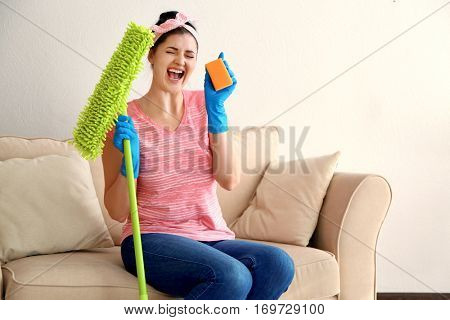 Happy young cleaner with dust mop and sponge sitting on sofa
