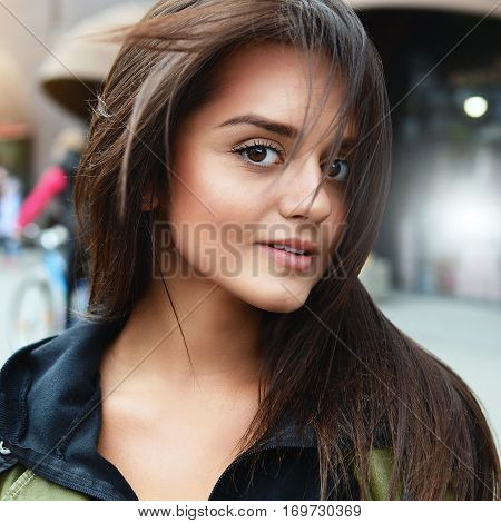 Portrait of a beautiful young girl brunette whose hair develop from a wind middle of the street. Casual comfortable clothing. Life style. Solar glare.