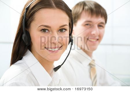 Portrait of beautiful telephone operator  looking at camera in working environment
