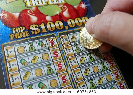Coquitlam BC Canada - November 20, 2016 : Close up woman scratching lottery ticket. The BC Lottery Corporation has provided government sanctioned lottery games in BC since 1985.