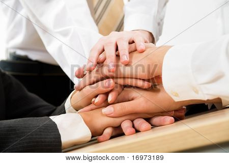 Image of business people hands on top of each other