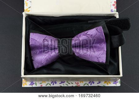 Purple Bow Tie In Present Box On Black Background