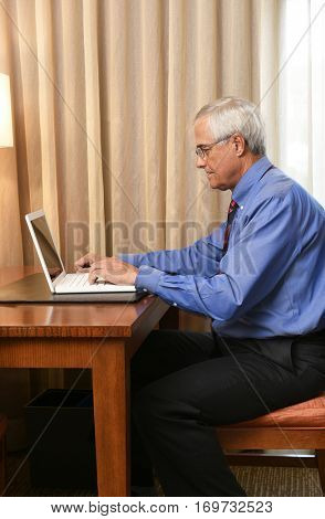 A senior businessman seated at the desk in his hotel room and working on his laptop computer. Vertical format.