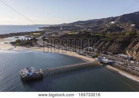 Aerial of historic Malibu Pier, Pacific ocean beaches and the Santa Monica Mountains in Southern California.