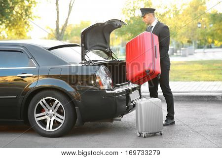Chauffeur putting suitcase in car trunk