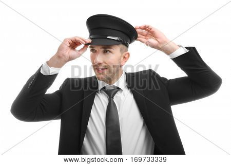 Young chauffeur adjusting his hat on white background