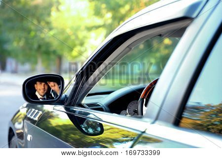 Chauffeur driving a car, view from reflection in mirror