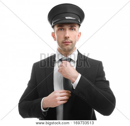 Young chauffeur adjusting tie on white background