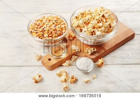 Bowls full of traditional popcorn and corn grain on wooden table