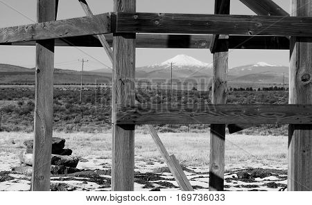 Mt. Jefferson in the distance framed by an old wooden structure with expanses of sagebrush and telephone poles in Brothers in the High Desert of Central Oregon on a winter day.