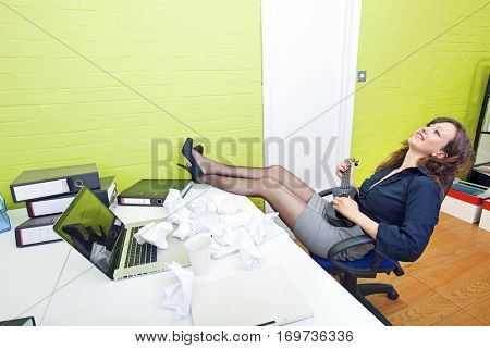 Businesswoman reclining at her desk playing ukulele
