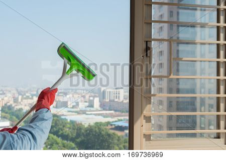 male cleaning glass window with brush and glove concept of domestic cleaning