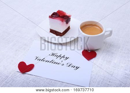 Close-up of white cup of coffee and strawberry cake. Red heart valentines day