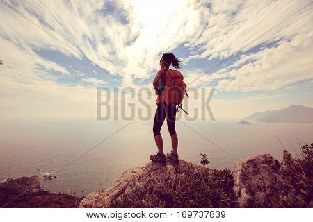 successful hiker hiking on seaside mountain peak