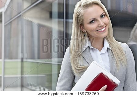 Portrait of beautiful businesswoman with organizer and digital tablet by glass wall