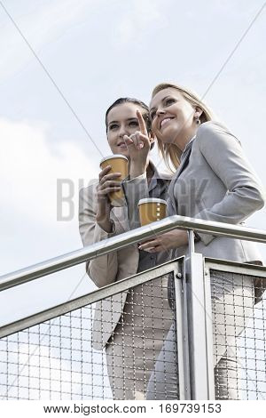 Young businesswoman with disposable coffee cup pointing while standing with coworker by railing against sky