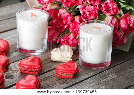 Red macaroons desserts and tulips on wooden background. dessert for breakfast on Valentine's Day.