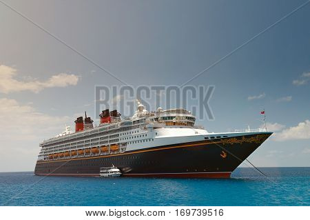 Classic black cruise ship in blue caribbean sea water and clear sky