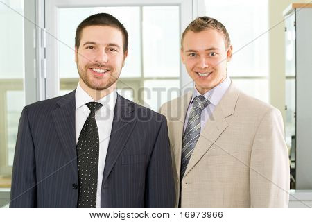 Two young businessmen smile and look at the camera