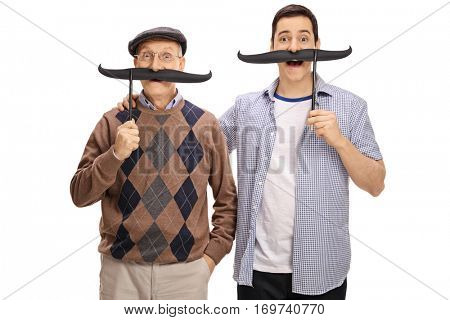 Senior and a young man posing with big fake moustaches isolated on white background