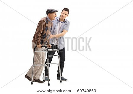 Full length portrait of a young man helping an elderly man with a walker isolated on white background