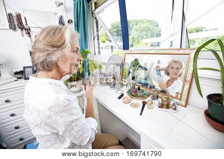 Senior woman combing her hair at dresser in house