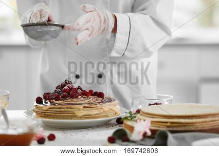 Cooking concept. Professional confectioner decorating tasty cake with sugar powder