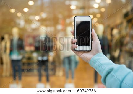 hands use smartphone taking photo front of shopwindow