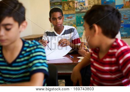Young people and education. Group of hispanic students in class at school during lesson. Frustrated boys cheating during admission test examination