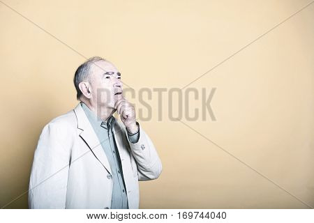 Senior adult man with his hand on his chin looking up inquisitively