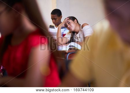 Young people and education. Group of hispanic students in class at school during lesson. Girl with headache sick female student