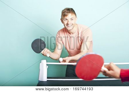 Caucasian man playing table tennis with friend