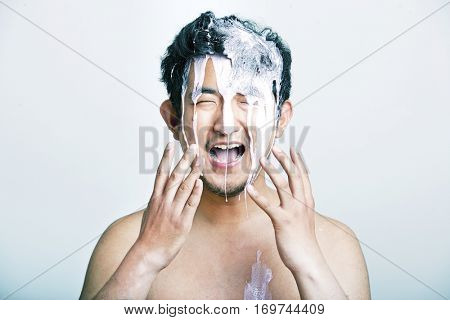 Shirtless young man with pink paint falling on his head against gray background