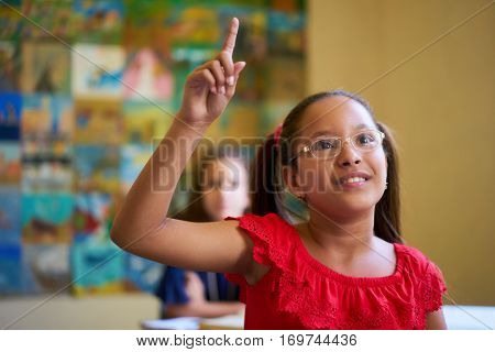 Young people and education. Group of hispanic students in class at school during lesson. Smart girl with eyeglasses raising hand