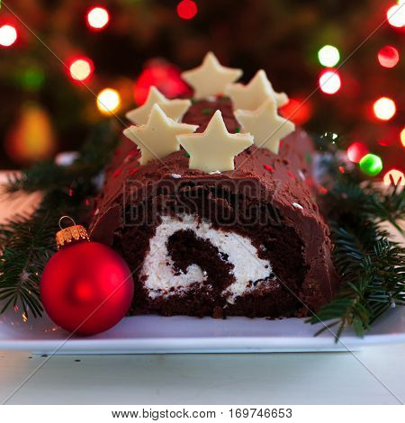 Homemade chocolate yule log Christmas cake against a background of Christmas lights.