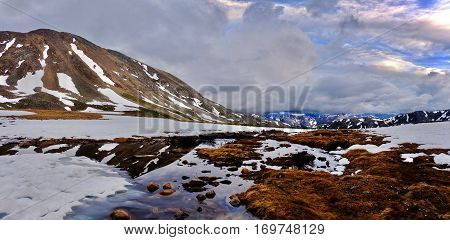 Storm clouds over mountains and reflection in water. Snow thawing on Independence Pass. Aspen. Colorado. United States.
