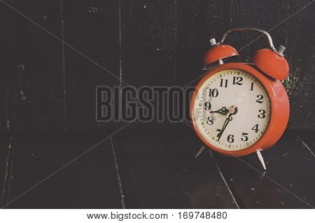 Red clock on back wood back ground