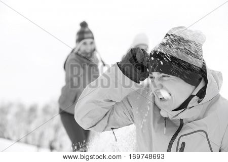 Young friends having snowball fight