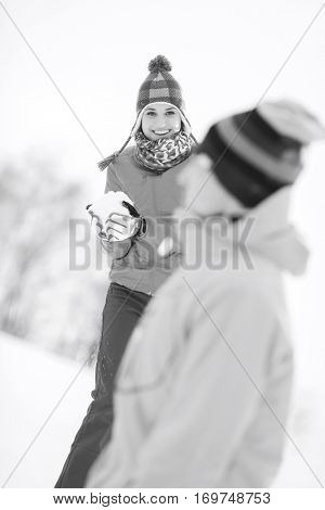 Smiling young woman having snowball fight with male friend