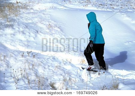 Young girl playing in the snow winter time coat hat boots wintery gloves