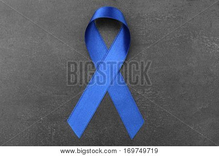 Blue ribbon on grey background. Colon cancer concept