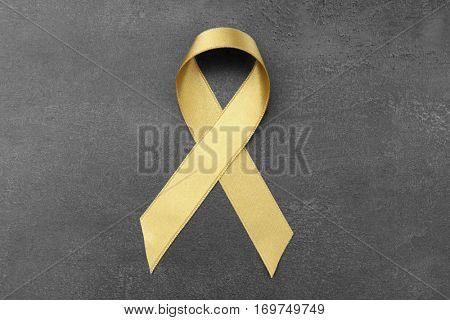 Golden ribbon on grey background. Children cancer concept