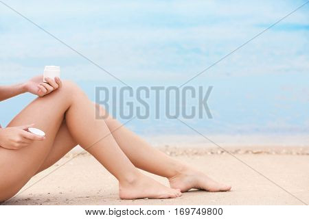 Young woman applying sun protective lotion on body at the beach