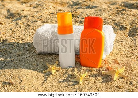 Towel, starfish and sunscreen cream on sea sand