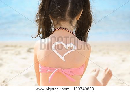 Cute little girl with sun block cream on back at beach