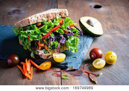 Vegan wholegrain sandwich with ingredients for healthy meal avocado micro greens super food diet concept selective focus toned image
