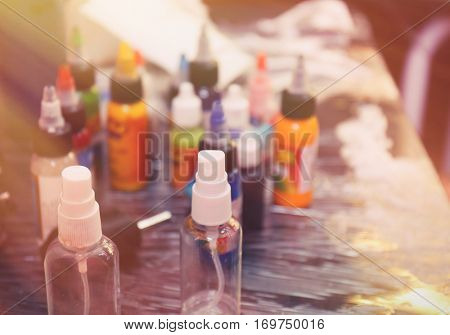 Bottles with inks and antiseptic on table in tattoo salon