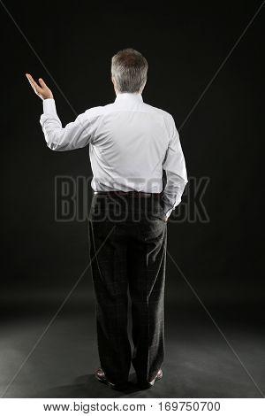 Senior businessman standing back on black background