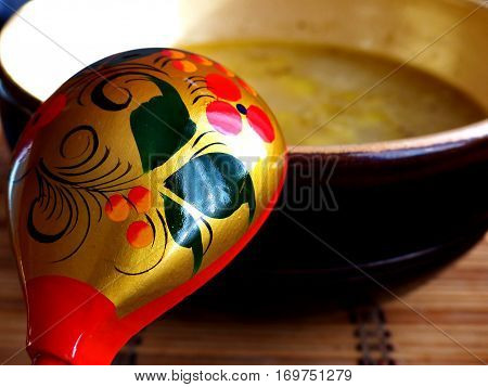 Khokhloma spoon and a bowl of soup. Closeup.  Khokhloma - an ancient Russian folk craft (XVII century). Traditional elements Khokhloma - red juicy berries of mountain ash and wild strawberries