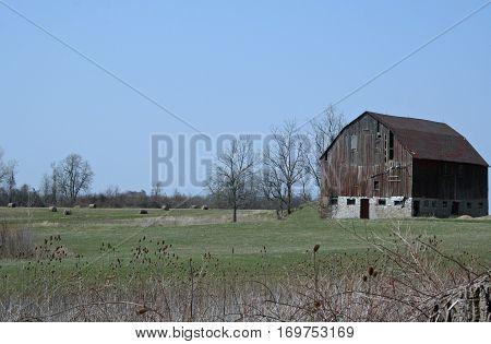 Old barn sitting in a quiet farm field